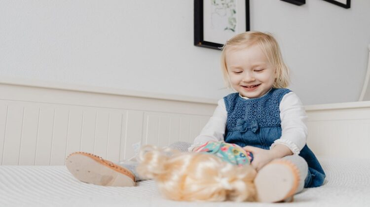 How To Help Your Child Develop Confidence Little girl in a blue dress playing with a doll