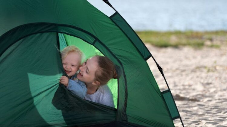 Mom and baby in tent pitched by a lake / Camping with Babies