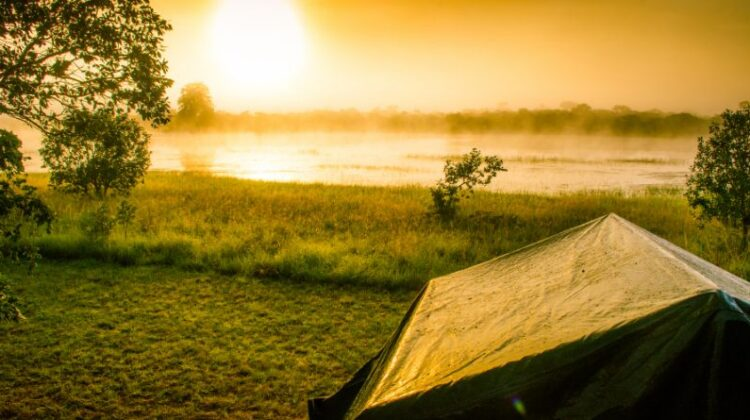 Camping Pitched Tent by a Lake at Sunrise