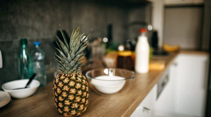 Popular Countertop Materials Wood Kitchen Countertop with fresh pineapple, bottle of milk, and bowls with ingredients