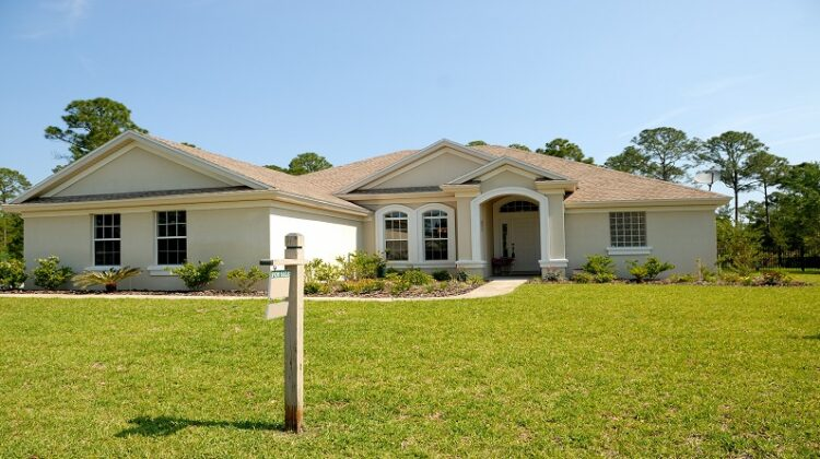 large beige home with white trim with for sale sign in yard