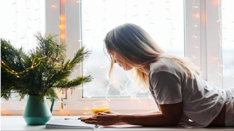 woman reading a book in front of window with fairy lights next to a vase filld with fir tree trimmings